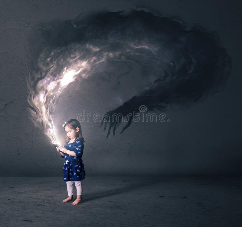 Little girl and cell phone. A little girl looks at a cell phone that has a dark monster royalty free stock photo