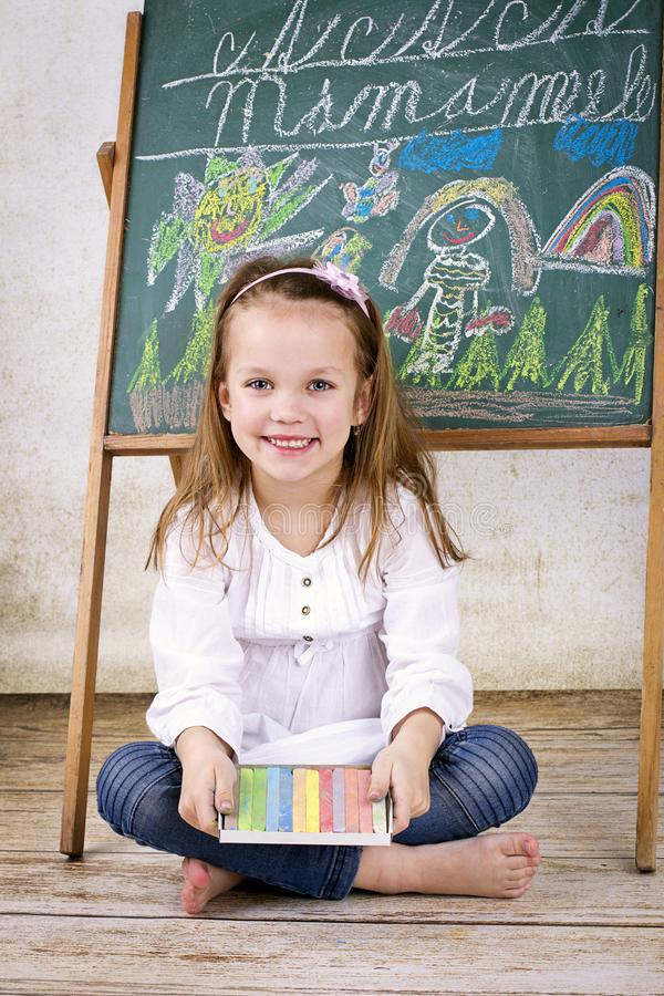 Little girl with chalks sitting in front of the blackboard. Studio portrait of pretty child at school stock photography