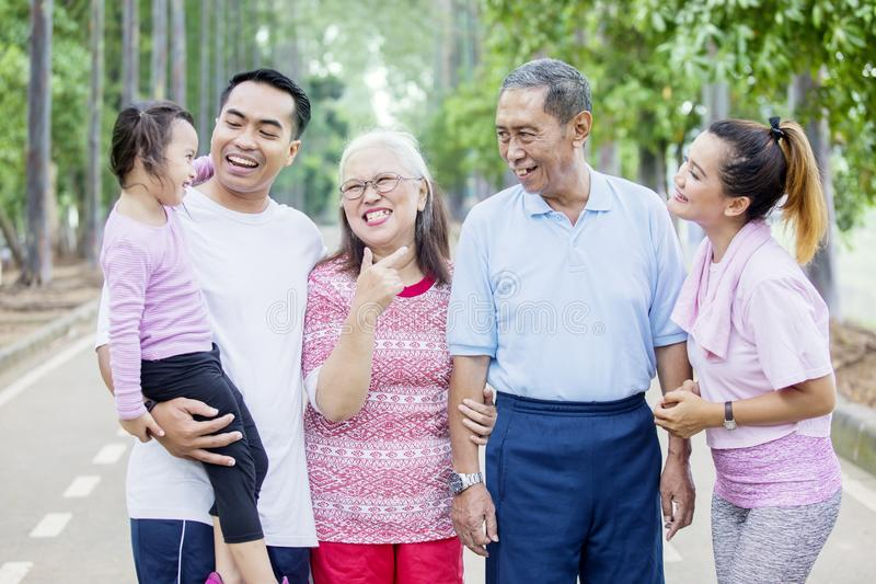 Little girl chats with her family in the park. Picture of little girl looks happy while chatting with her grandparents and parents in the park stock photography