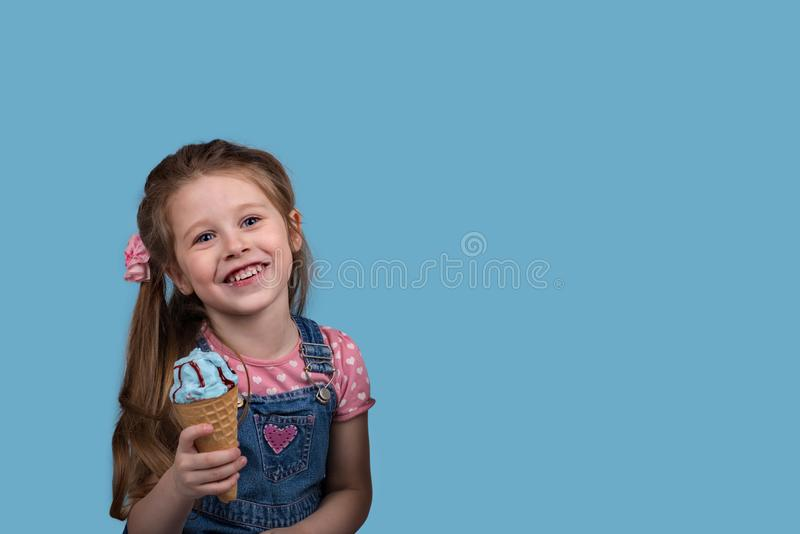 The little girl cheerfully eats ice cream in wafer gunny on bl. Close up emotional portrait of the smiling little girl on blue background in studio with copy royalty free stock photography
