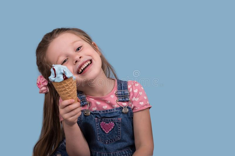 The little girl cheerfully eats ice cream in wafer gunny on bl. Close up emotional portrait of the smiling little girl on blue background in studio. She stock photo