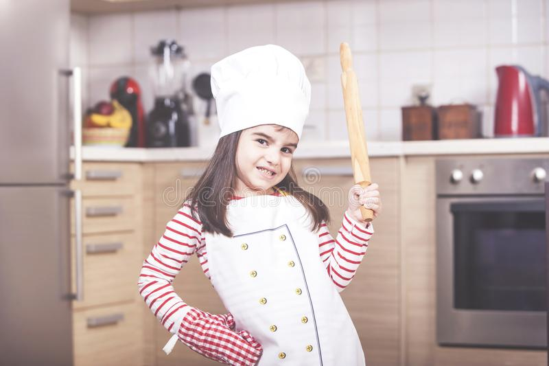 Little girl chef in the kitchen stock images