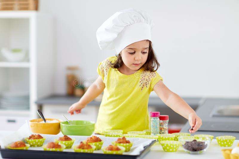 Little girl in chefs toque baking muffins at home. Family, cooking and people concept - little girl in chefs toque baking muffins or cupcakes with sprinkles at stock photo