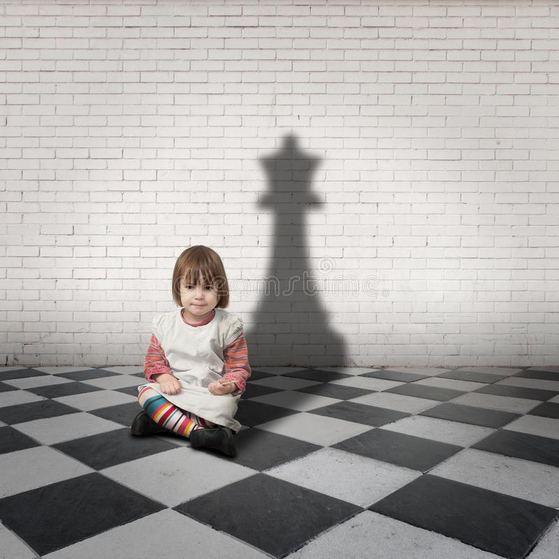 Little girl with a chess queen shadow stock photography
