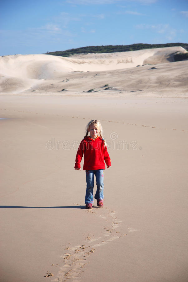 Little girl child on beach. Full body of a cute little Caucasian girl child with blond hair with happy smiling facial expression walking backwards in the sand on stock photos