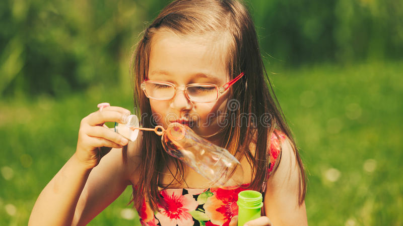 Little Girl Child Blowing Soap Bubbles Outdoor. Stock