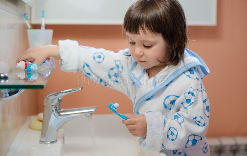A little girl or child brushes teeth in the bathroom. Hygiene of the oral cavity. stock photo