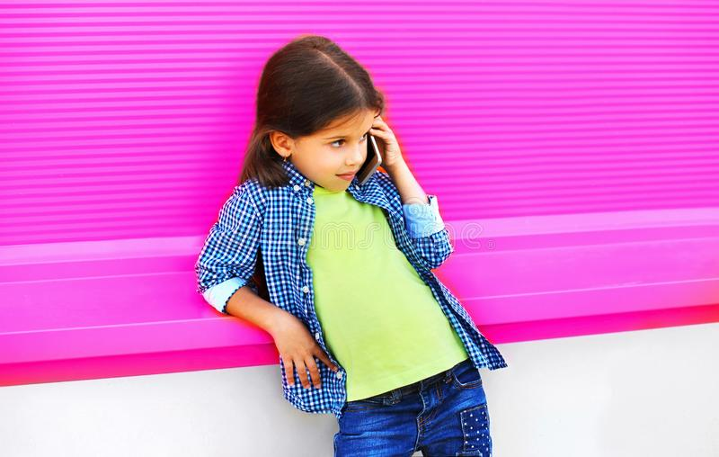 Little girl child calling on smartphone on city street on colorful pink wall royalty free stock image