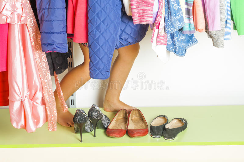 Little girl child choosing clothes to wear in wardrobe. Beautiful legs. Fashion clothing sale concept.  stock photography