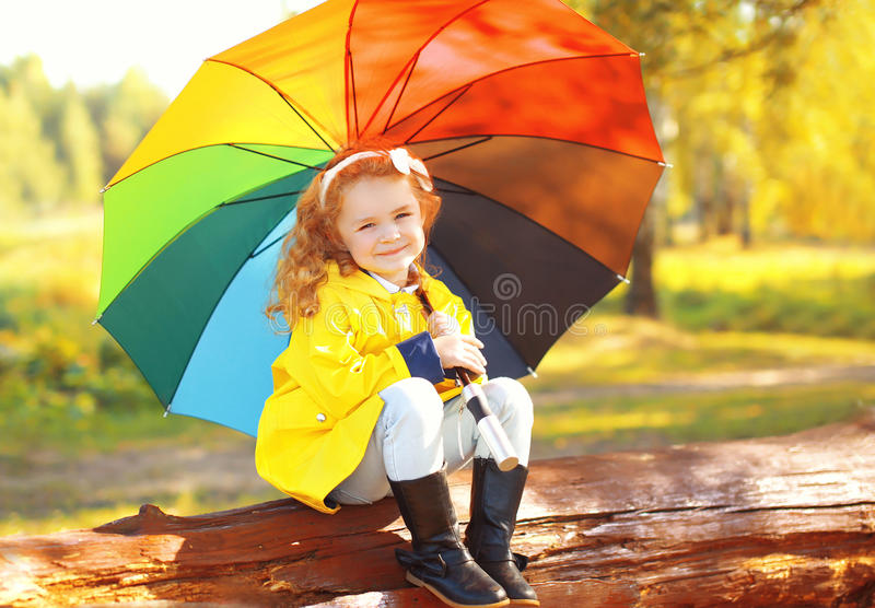 Little girl child with colorful umbrella in sunny autumn. Park stock image