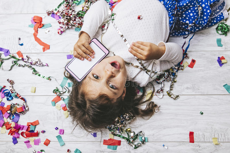 Little girl child cute and beautiful with multi-colored confetti royalty free stock image