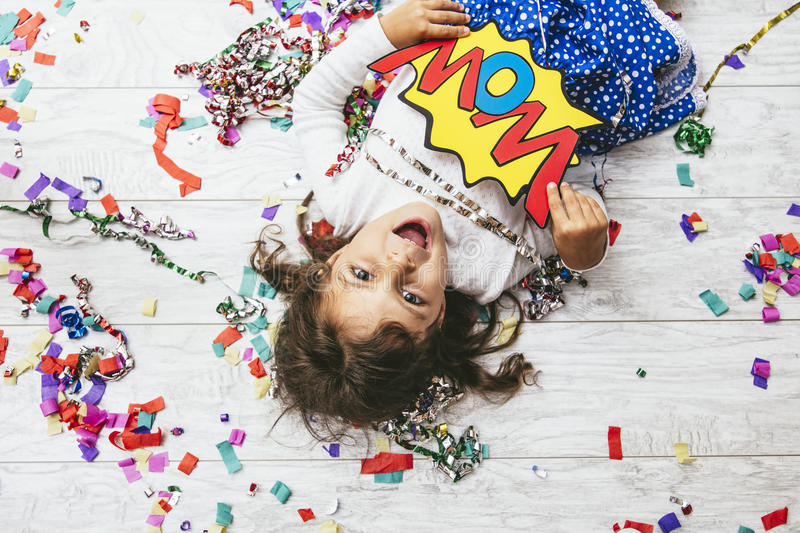 Little girl child cute and beautiful with multi-colored confetti. On the floor happy happy with a sign wow royalty free stock images