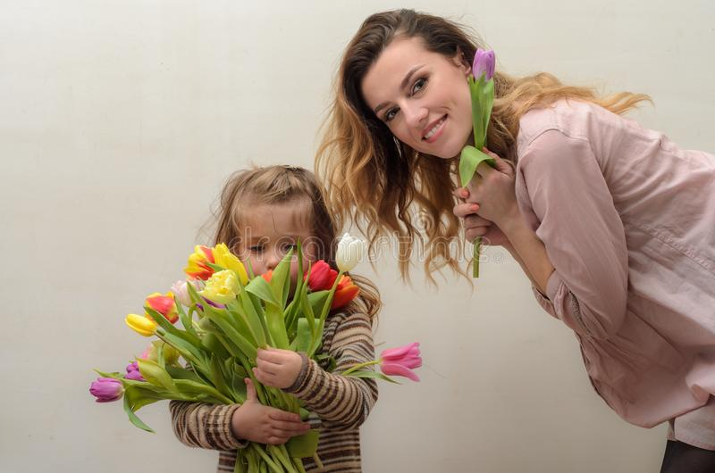 Little girl child, daughter gives mom a bouquet of flowers of colorful tulips - happy family royalty free stock photography