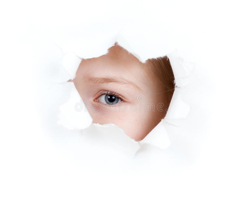 Little girl child eye in torn paper hole stock photos