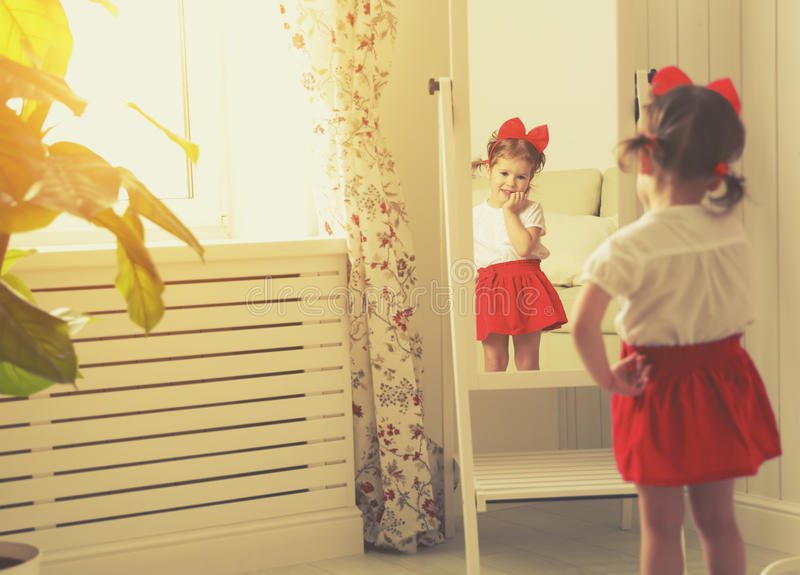 Little girl child fashionista looking in the mirror at home. In a red skirt, shoes of mother royalty free stock photography
