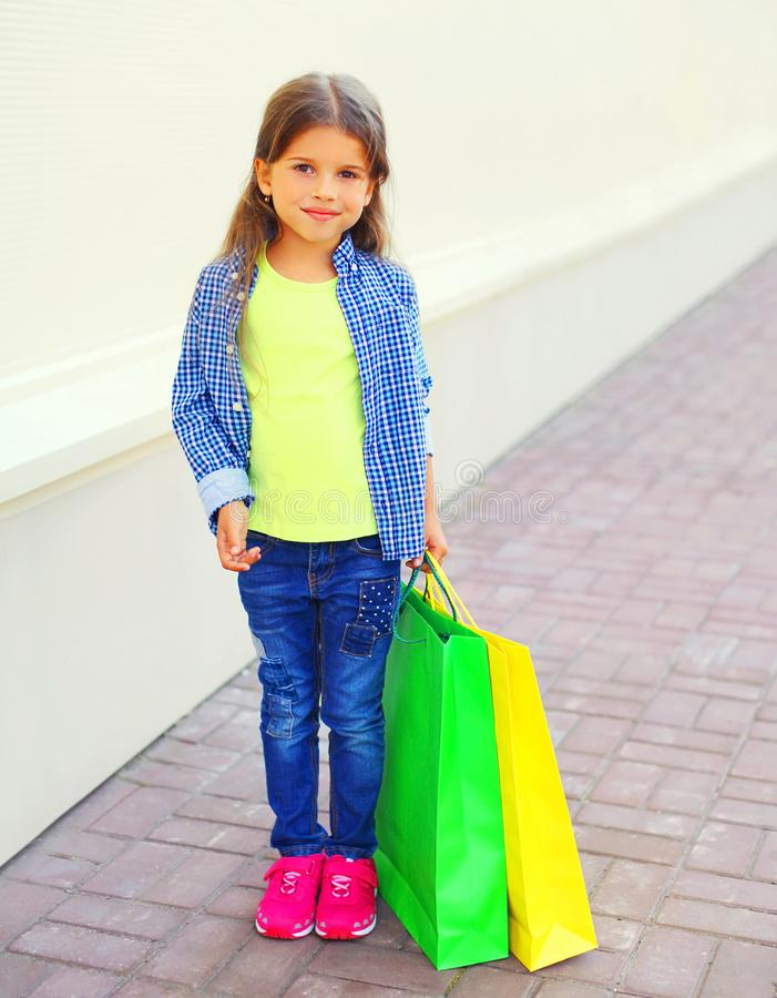 Little girl child holds shopping bags in city royalty free stock photography