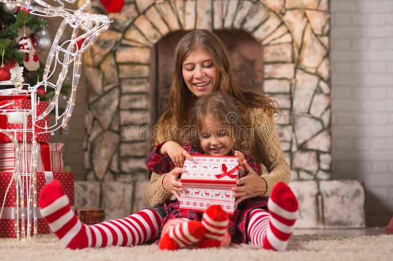 Little girl child at home by the fireplace with the family parent mother and Christmas tree with gifts and luminous garlands. Merry Christmas. Little girl child royalty free stock image