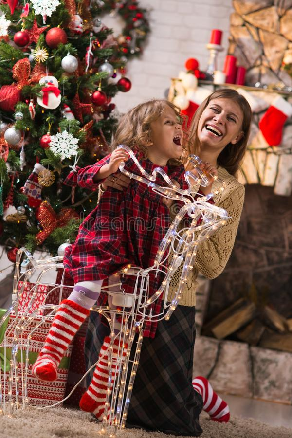 Little girl child at home by the fireplace with the family parent mother and Christmas tree with gifts and luminous garlands. Merry Christmas. Little girl child stock photos