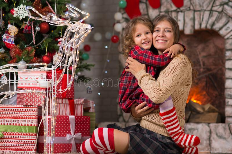 Little girl child at home by the fireplace with the family parent mother and Christmas tree with gifts and luminous garlands. Merry Christmas. Little girl child stock image