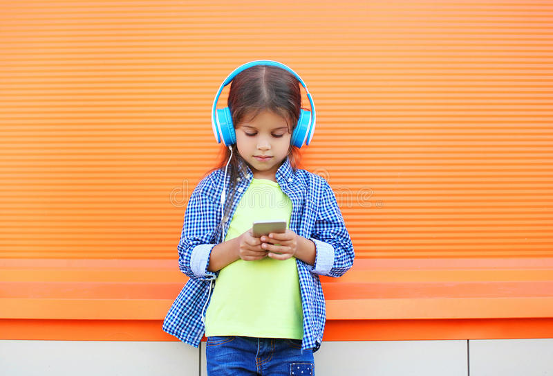 Little girl child listens to music in headphones and using smartphone stock photography