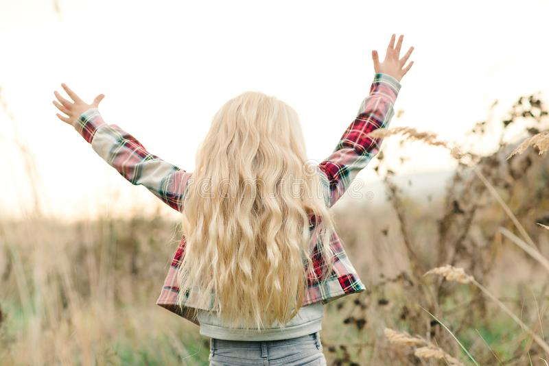 Little girl child with long blondy wavy hair. Happy child raise up hands at sunset at nature. Beautiful warm summer evening. Kids stock photos