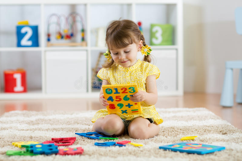 Little girl child playing with lots of colorful plastic digits or numbers indoors. royalty free stock photo