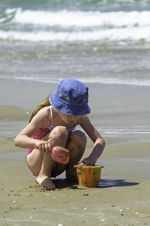 Little girl child playing with the sand in the sea stock images