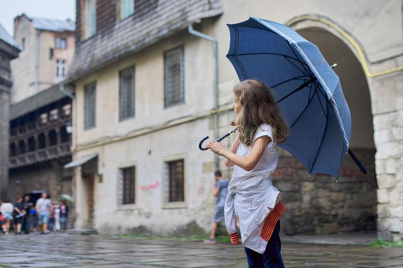 Little girl child in the rain with an umbrella, tourist old city background stock images