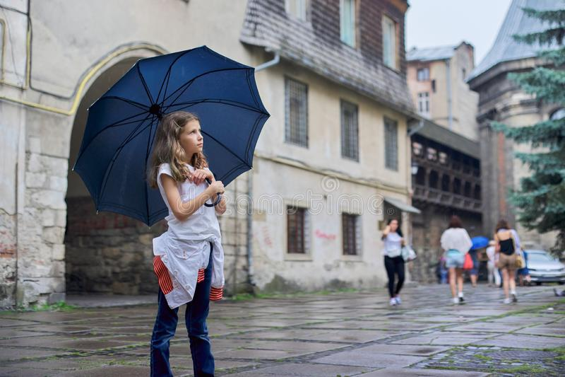 Little girl child in the rain with an umbrella, tourist old city background stock photo