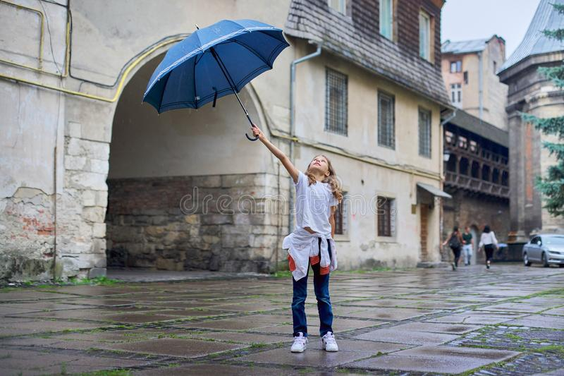 Little girl child in the rain with an umbrella, tourist old city background royalty free stock photography