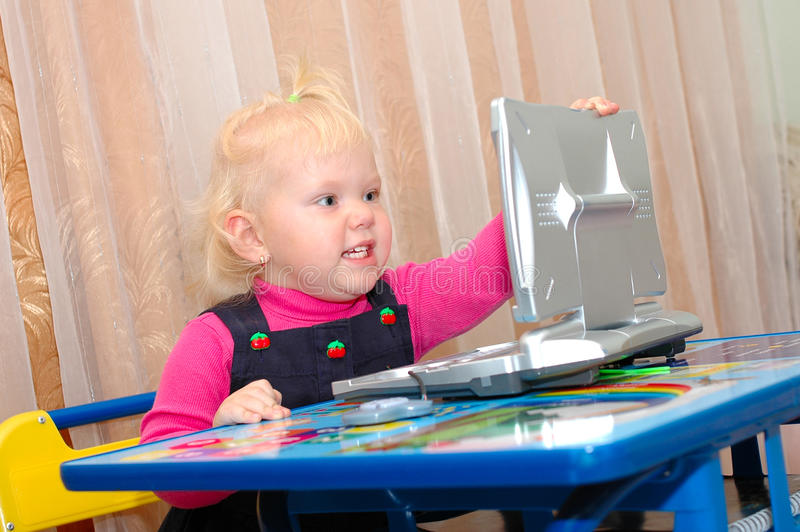 Little girl with child's computer (notebook). royalty free stock photography