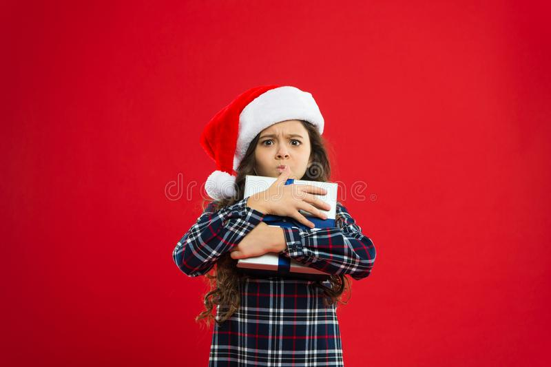 Little girl child in santa red hat. Christmas shopping. Happy winter holidays. Small naughty girl. Present for Xmas royalty free stock images