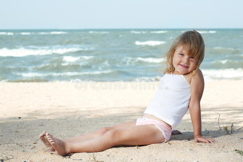 Little girl child on the sea. Under blue sky stock photos