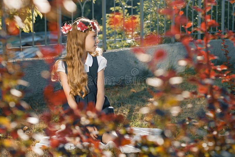 Little girl child sitting on lawn, girl blonde with long wavy hair with wreath of pink flowers royalty free stock photo