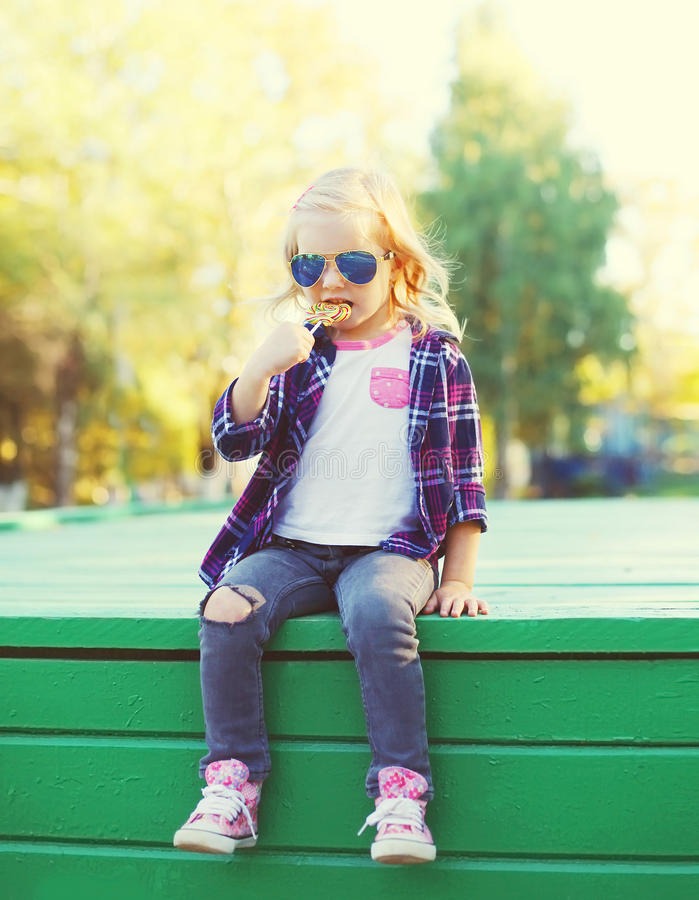 Little girl child sitting with sweet lollipop in city stock images