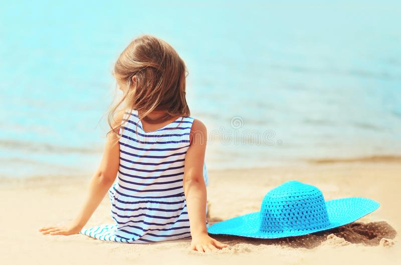 Little girl child in striped dress with summer straw hat sitting on sand beach stock image