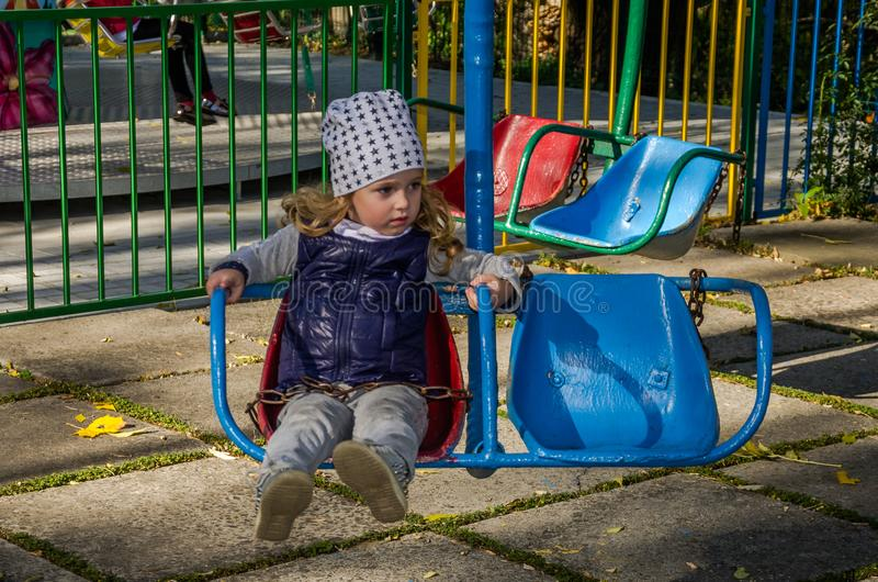 Little girl child swinging on a swing in an amusement park royalty free stock image