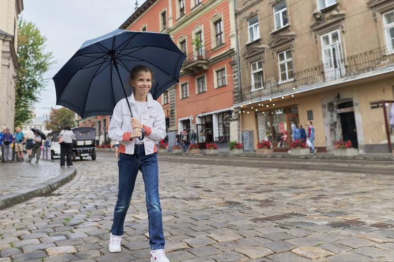 Little girl child walking with an umbrella on a city street stock image