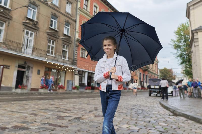 Little girl child walking with an umbrella on a city street royalty free stock photos