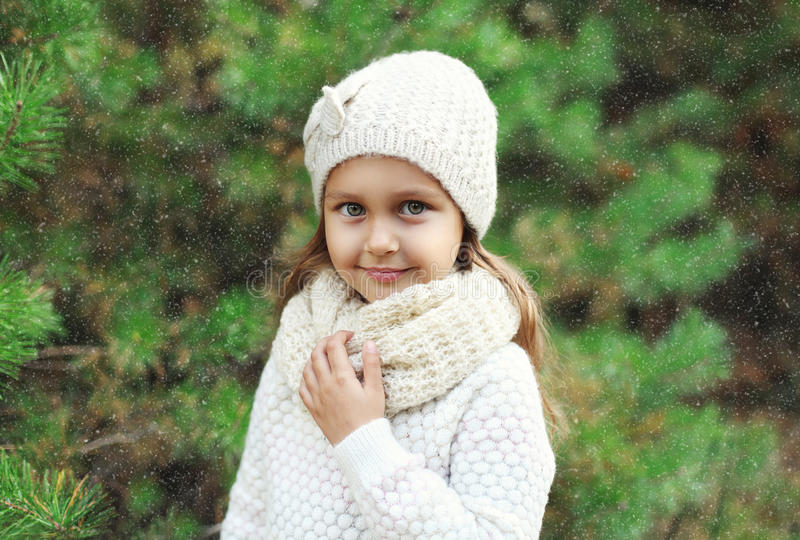 Little girl child wearing knitted hat and sweater with scarf near christmas tree royalty free stock image