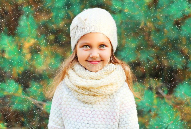 Little girl child wearing knitted hat sweater with scarf over christmas tree stock photo