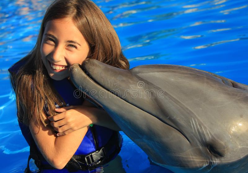 Little girl children kissing a gorgeous dolphin flipper smiling face happy kid swim bottle nose dolphins. At aquarium high quality picture stock image