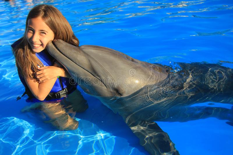 Little girl children kissing a gorgeous dolphin flipper smiling face happy kid swim bottle nose dolphins. Little girl children swimming with a gorgeous dolphin royalty free stock images