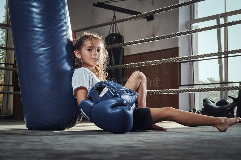 Little girl is chilling after competition at boxing ring stock photos