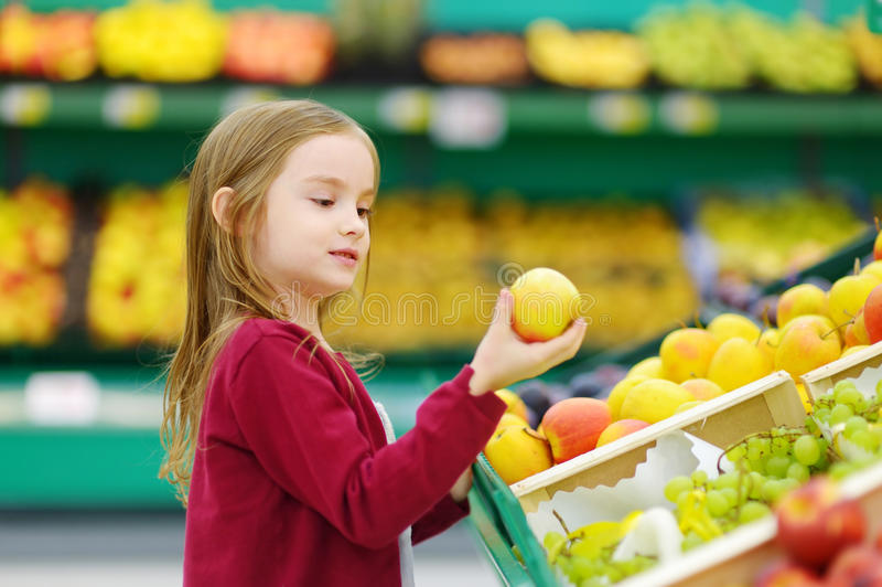 Little girl choosing an apple in a store royalty free stock photo