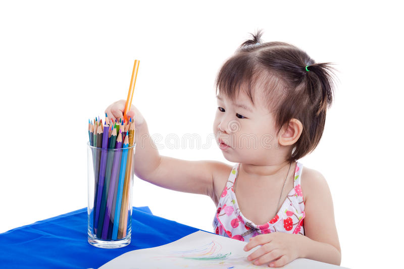 Little girl choosing colour pencil for draw picture. Little girl sitting at the table and choosing colour pencil for draw picture, on white background royalty free stock images