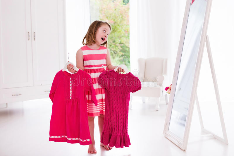 Little girl choosing dresses in white bedroom. Child watching mirror reflection holding pink dress choosing outfit. Girls nursery. Shopping clothing for kids stock photos