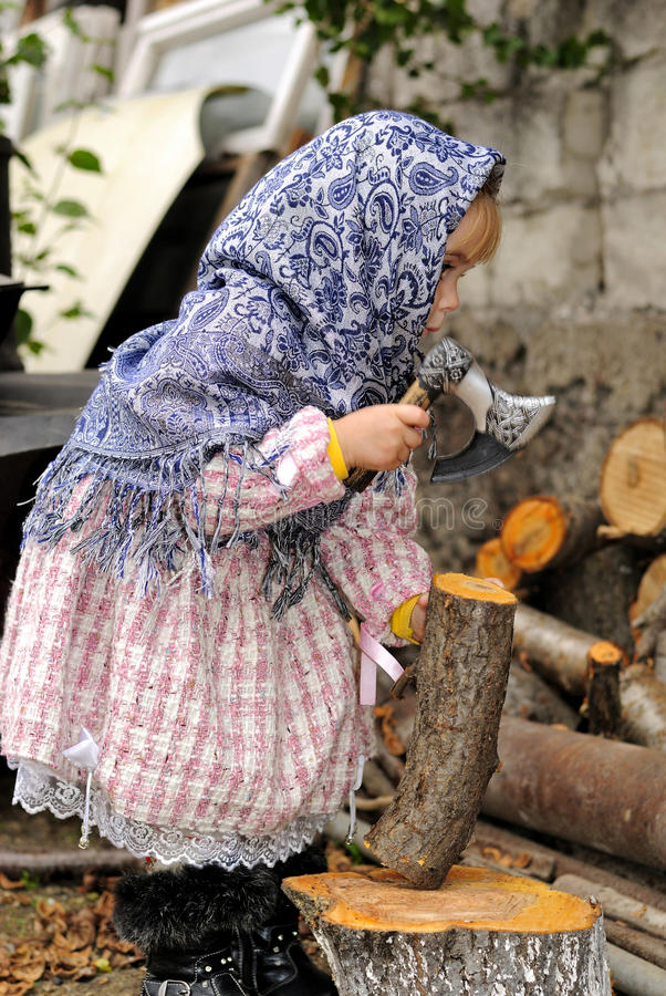The Little Girl  Chops Firewood An Axe Royalty Free Stock Images