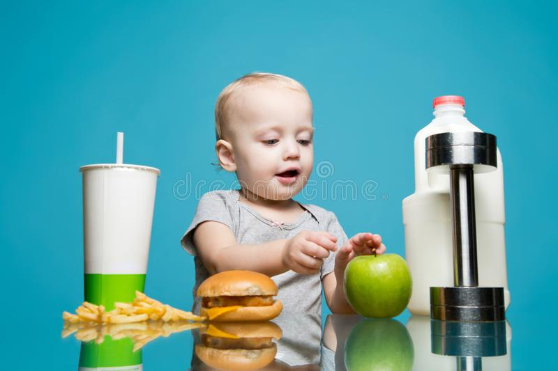 A little girl chose healthy food instead of harmful and grabs an apple stock image