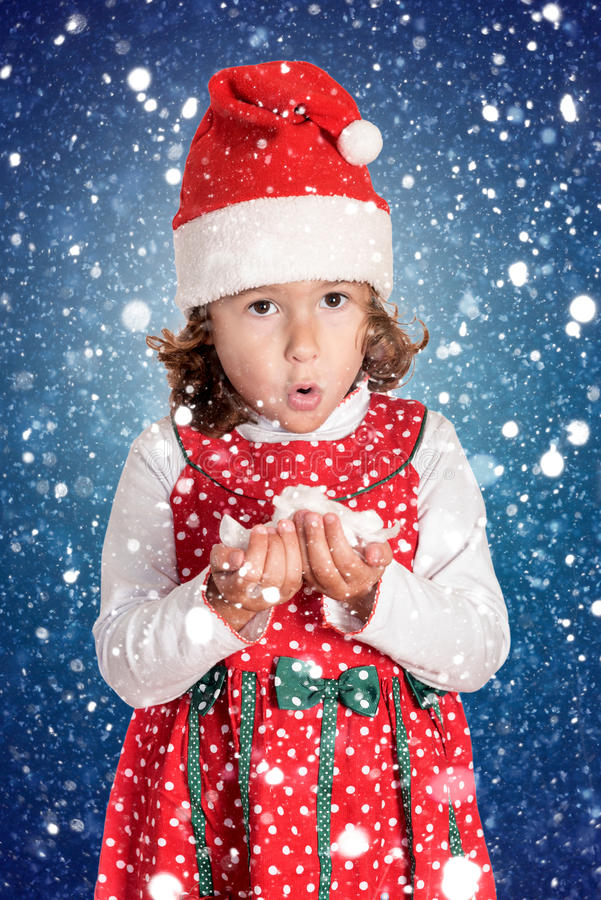 Little girl in Christmas blowing snowflakes. Portrait of little girl in Christmas dress blowing snowflakes royalty free stock images